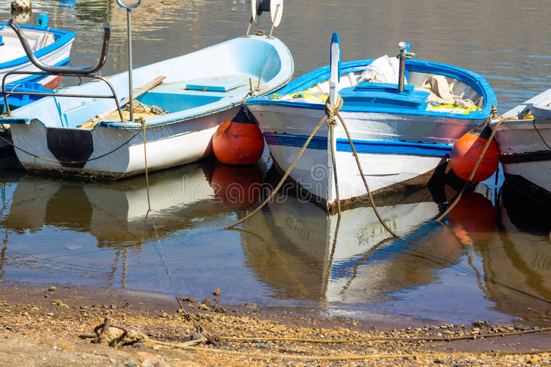 Gamla fiskebåtar som binds till kusten med det lugna havet och reflexion royaltyfri bild