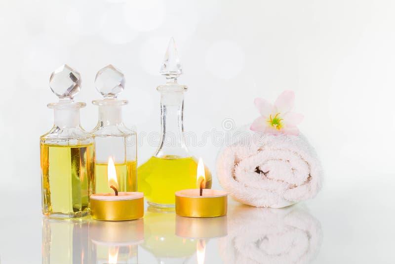 Gamla flaskor för tappning av aromatiska oljor med brända stearinljus, blommor och den vita handduken på den glansiga vita tabell royaltyfria bilder