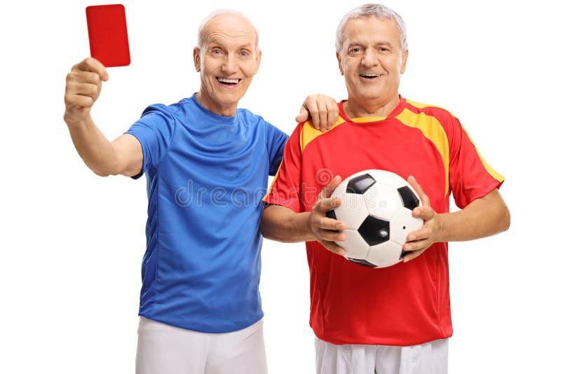 Gamla fotbollspelare med ett rött kort och en fotboll royaltyfri bild