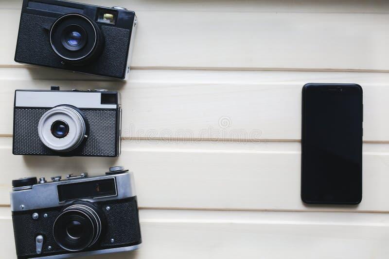 Gamla fotokameror och svart smartphone på trätextur Tappningfilmkamera med på beige bakgrund Retro och antikt arkivbilder