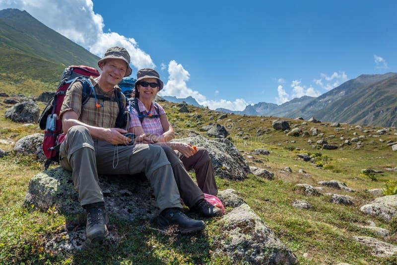 gamla fotvandrare med stora ryggsäckar som vilar på berget Kackarlar arkivfoton