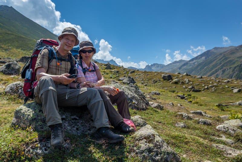gamla fotvandrare med stora ryggsäckar som vilar på berget Kackarlar arkivfoto