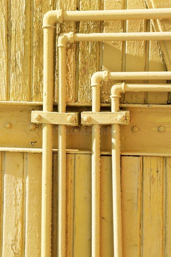 Gamla gula rör på träväggen Bakgrund för skrapaGrungeUrban land Textur f?r din design fotografering för bildbyråer