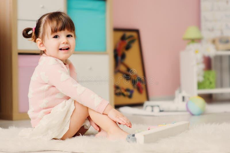 Gamla gulliga lyckliga 2 år behandla som ett barn flickan som spelar med hemmastadda leksaker arkivfoton