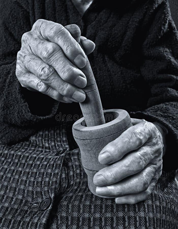 Gamla händer som rymmer trämortel. royaltyfri bild