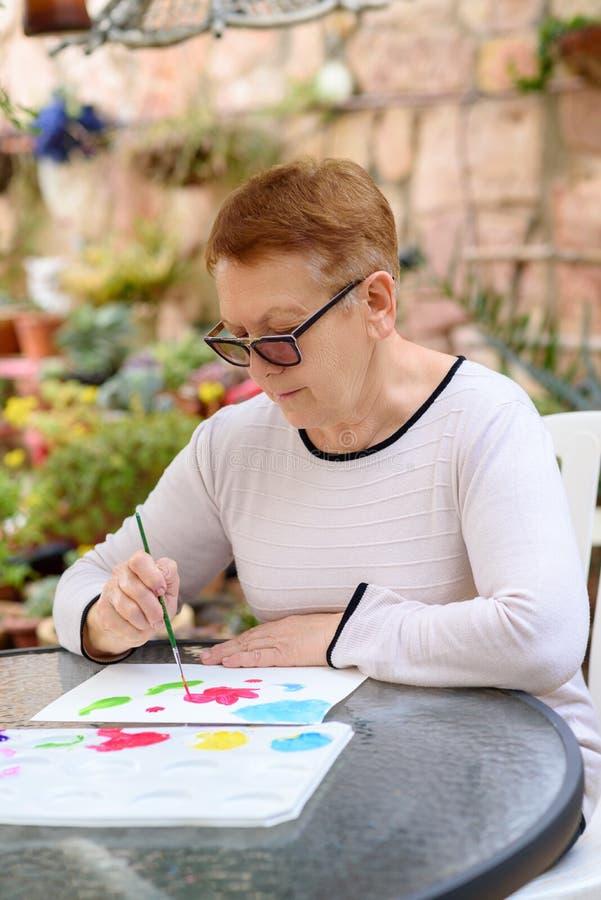 Gamla höga kvinnor som har rolig målning i utomhus- konstgrupp royaltyfri foto