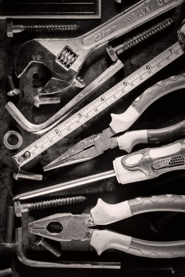 Gamla hjälpmedel och skruvar på en metallisk bakgrund arkivbilder