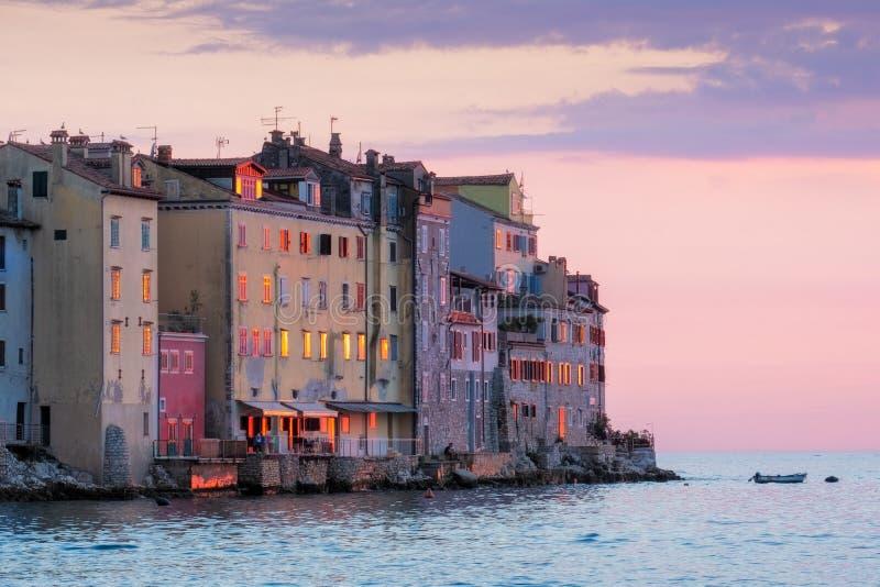 Gamla hus på havet seglar utmed kusten på den färgrika solnedgången i Rovinj, Kroatien arkivfoton