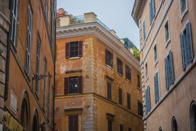 Gamla hyreshusar i Rome, orange färg av fasader, fönster med slutare royaltyfri foto