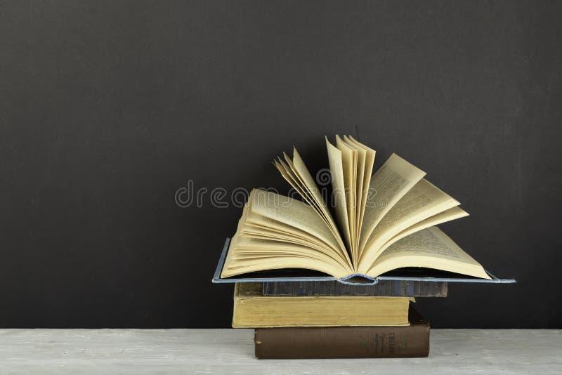 Gamla inbunden bokböcker för tappning, fläktade sidor på röd bakgrund tillbaka skola till kopiera avstånd sax och blyertspennor p fotografering för bildbyråer
