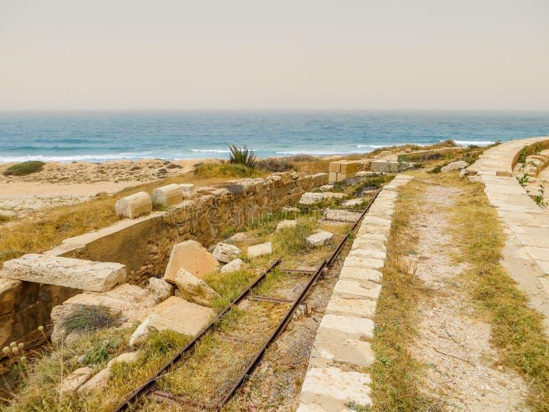 Gamla italienska järnvägspår bland forntida romare fördärvar på den medelhavs- kusten av Libyen på Leptis Magna royaltyfri foto