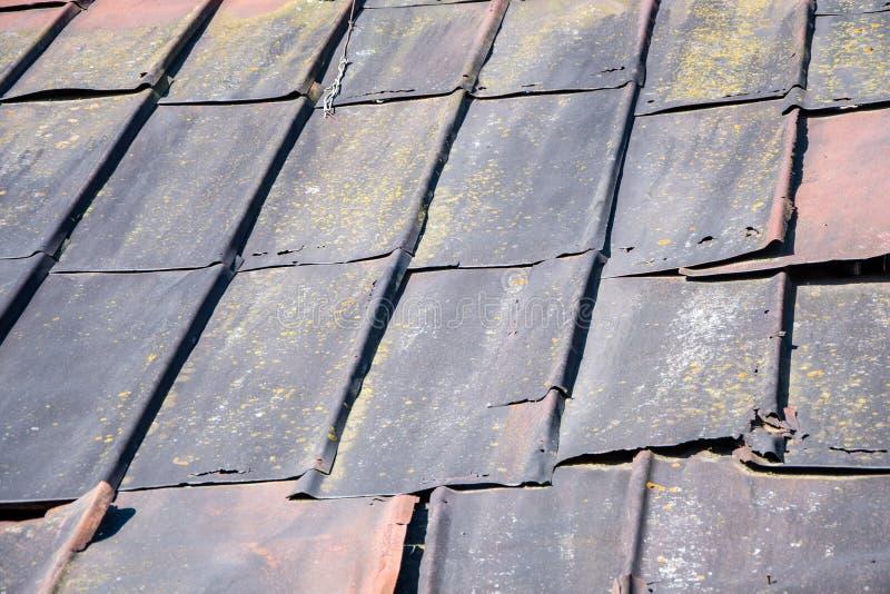Gamla järnskivor på husets tak, förstörelse av byggnadens tak, en förfallen struktur royaltyfria bilder
