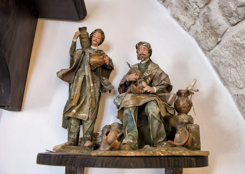 Gamla kanstödda skulpturmän som arbetar producera olivolja på Masseria Il Frantoio, sydliga Italien fotografering för bildbyråer
