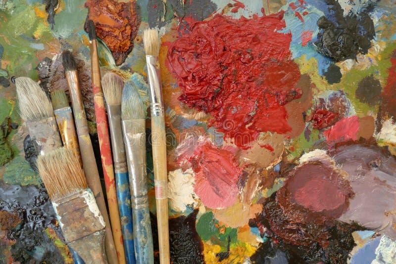 Gamla konstborstar på en palett med målarfärger Top beskådar arkivfoton