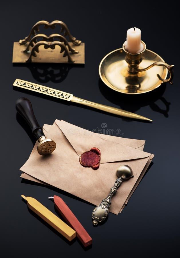 Gamla kuvert med den röda vaxskyddsremsan, bokstavsöppnaren och bokstavshållaren royaltyfri foto