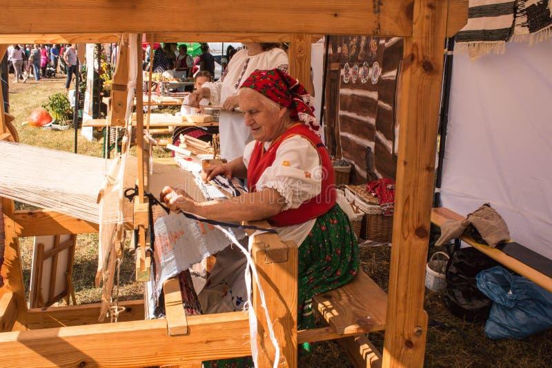 Gamla kvinnor som gör den traditionella handen - gjord knuten löparematta på trävävstolen arkivbild