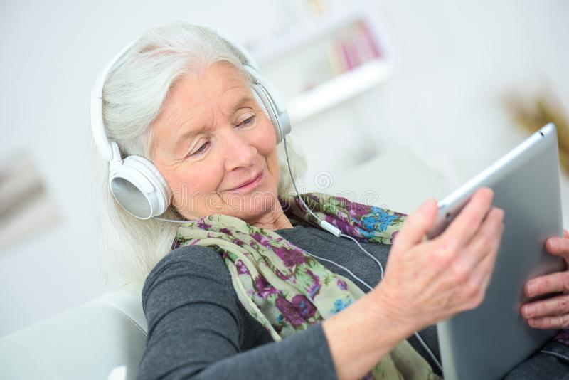Gamla kvinnor som lyssnar till musik från labtop royaltyfri fotografi