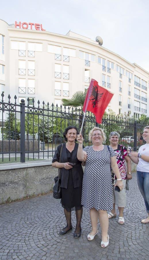 Gamla kvinnor som rymmer nationsflaggan i Tairna, Albanien royaltyfria bilder