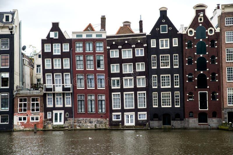 Gamla lutande kanalbyggnader i Amsterdam arkivfoto