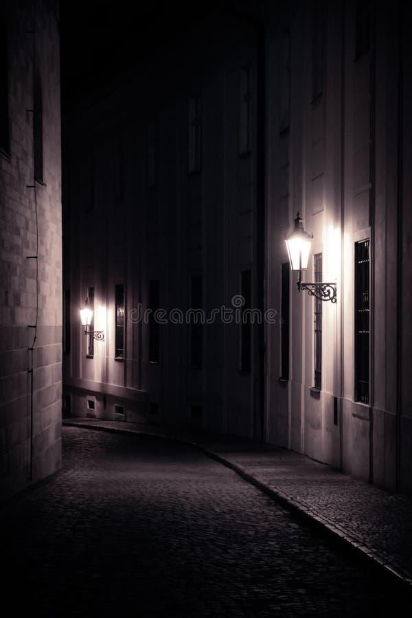 Gamla lyktor som exponerar en medeltida gata för mörk bakgata på natten i Prague, Tjeckien Monochromatic foto i lodlinje arkivfoto