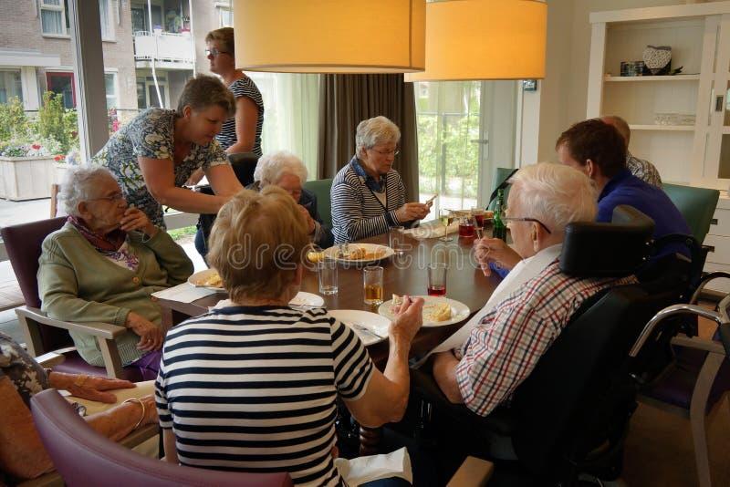 Gamla människor i ett vårdhem som har matställen royaltyfria foton