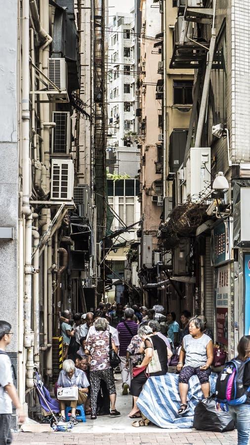 Gamla m?nniskor samlar i skuggan under hyreshusar i Hong Kong royaltyfri fotografi