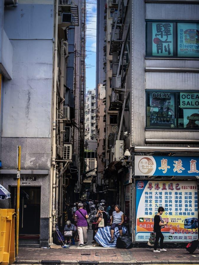 Gamla m?nniskor samlar i skuggan under hyreshusar i Hong Kong arkivfoto