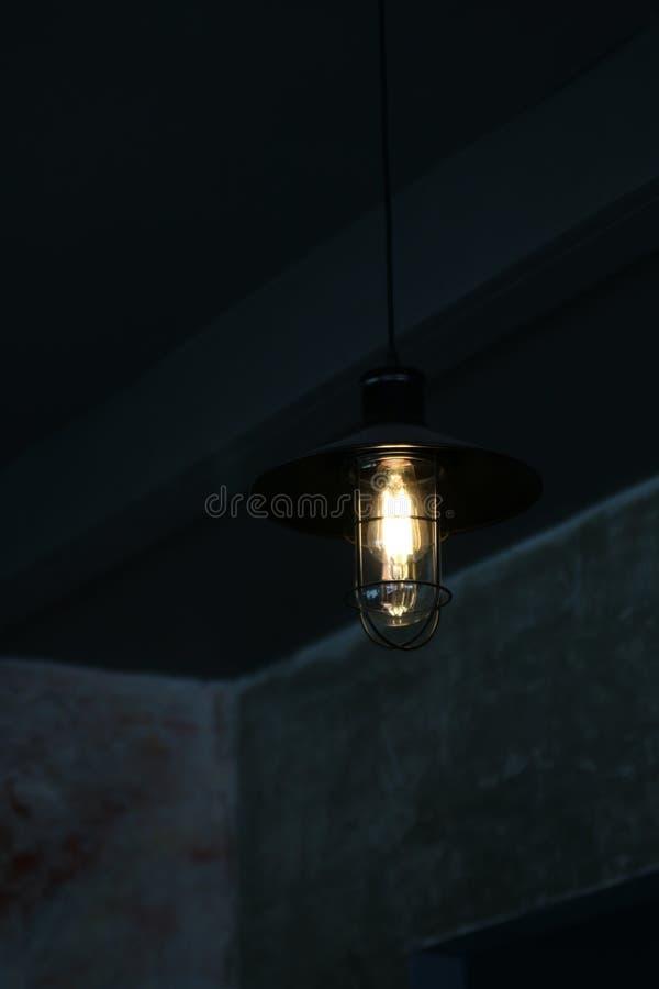 Gamla moderna lampor som hänger på väggen i den mörka konstgjorda lampan, dekorerar i mörkret arkivbild