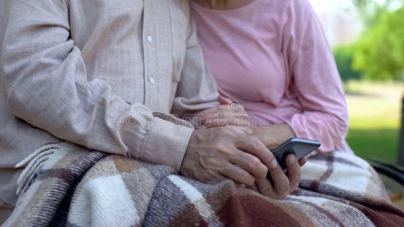 Gamla morföräldrar som håller ögonen på familjfoto i smartphonen som in kopplar av, parkerar, grejen royaltyfri bild