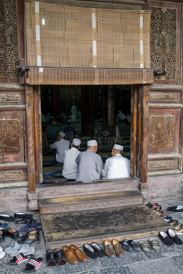 Gamla muslimska kinesiska män som ber på Xian Great Mosque i staden av Xian Den stora moskén som lokaliseras i mitten av staden arkivbilder