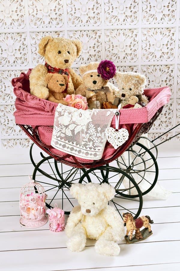 Gamla nallebjörnar och leksaker i tappningbarnvagn arkivfoton