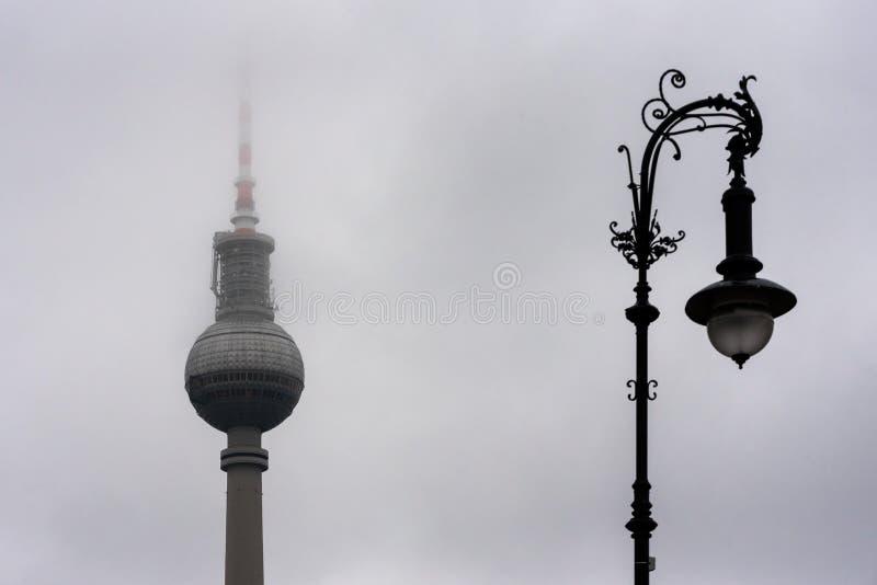 Gamla och nya Berlin - TVtorn och en gatalampa i dimma royaltyfri fotografi