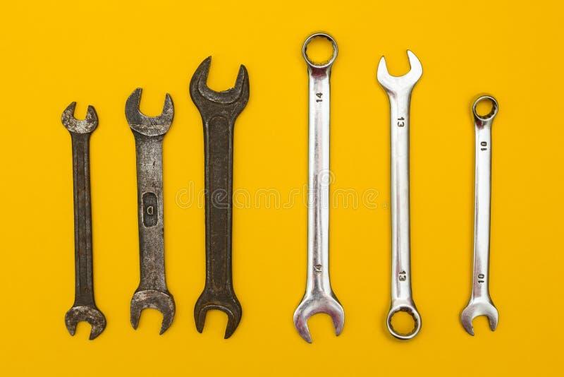 Gamla och nya skiftnycklar på en gul bakgrund arkivfoto