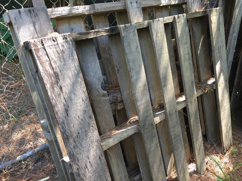 Gamla paletter som lutar upp mot ett staket för chain sammanlänkning royaltyfri fotografi