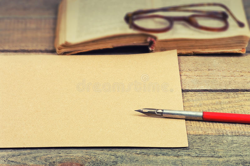 Gamla papper, penna, bok och exponeringsglas arkivbild