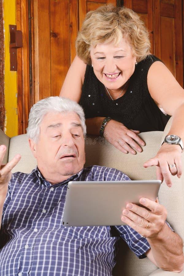 Gamla par genom att använda minnestavlan arkivfoton
