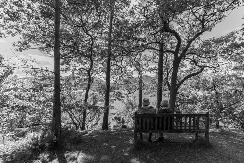 Gamla par på bänken, Derwent vatten sjö, Keswcik, UK-monokrom arkivbild