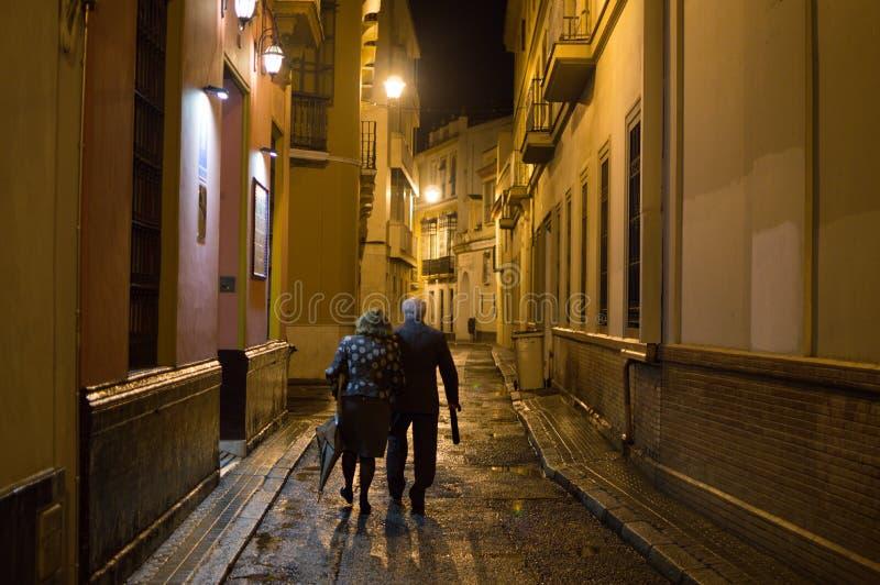 Gamla par som går i Seville på natten, Spanien arkivfoton