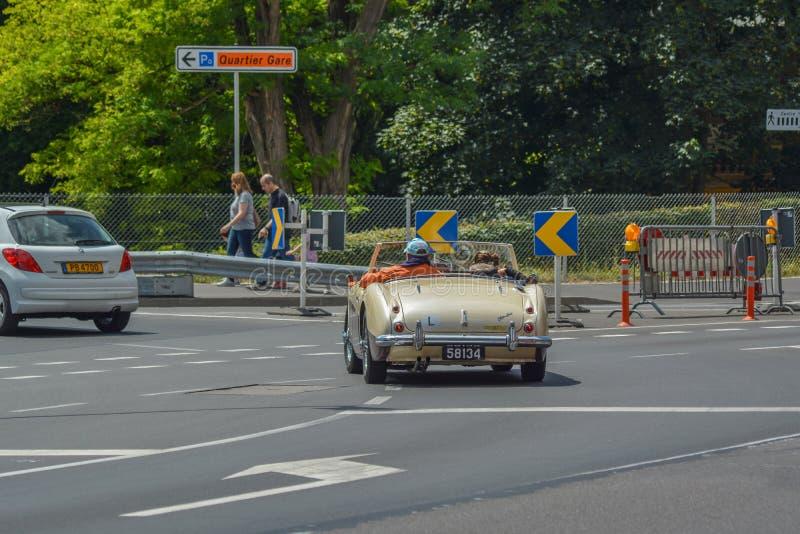 Gamla par som kör den klassiska bilen royaltyfri foto