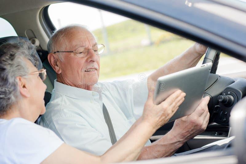 Gamla par som kör den nya bilen fotografering för bildbyråer