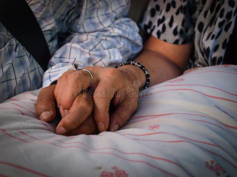 Gamla par som rymmer sig händer arkivbilder