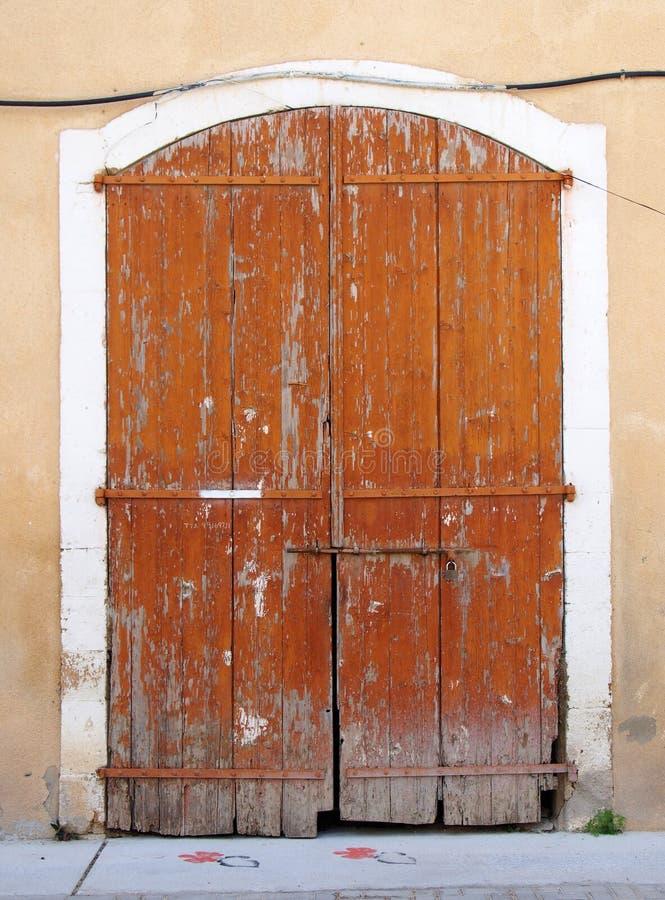Gamla pittoreska förfalla brunt målade trädubbla dörrar som kasta i sig som stängs med en hänglåsuppsättning i en vit stenram arkivfoto