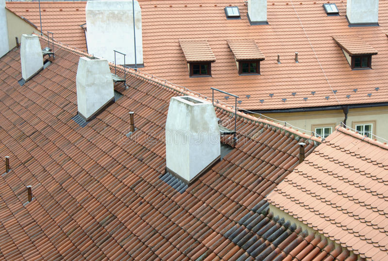Gamla röda tak med tegelplattor och vitlampglas i Prague arkivfoton