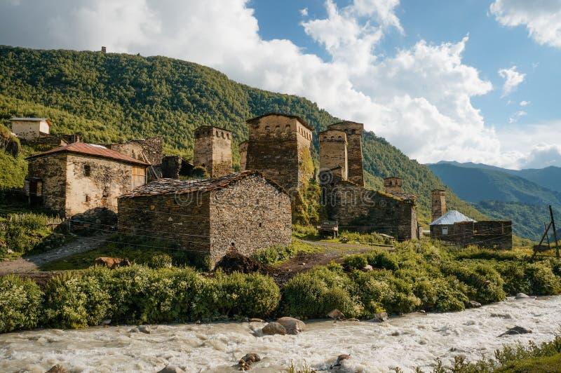 gamla red ut byggnader mot den lilla floden strömmar mot kullar, Ushguli, royaltyfri foto