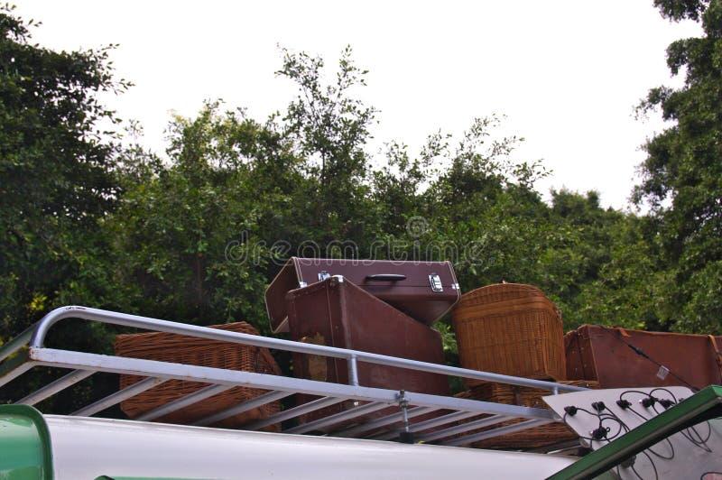 Gamla resväskor på taket på en bil med träd i bakgrunden arkivbild