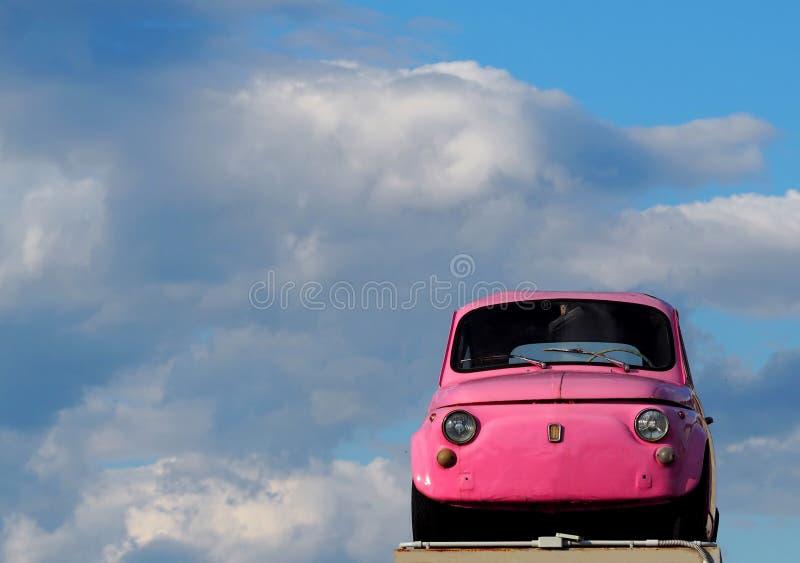 Gamla rosa färger 500 fiat under en tappningbil som samlar främre sikt med endast himmel och moln på bakgrunden arkivfoto
