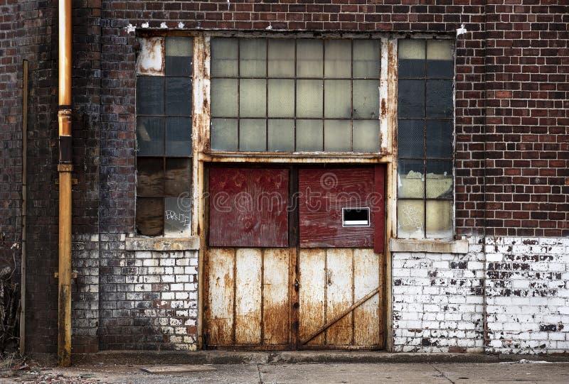 Gamla rostade metalldörrar på övergiven förfalla tegelstenfabriksbyggnad arkivfoto