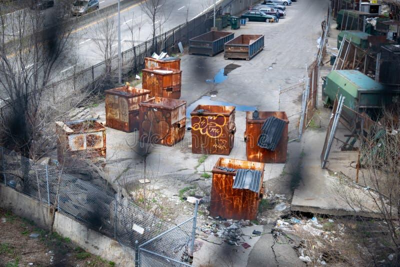 Gamla rostiga konstruktionsbeh?llare och dumpsters p? en delapidated bakgata i New York City, USA royaltyfri fotografi