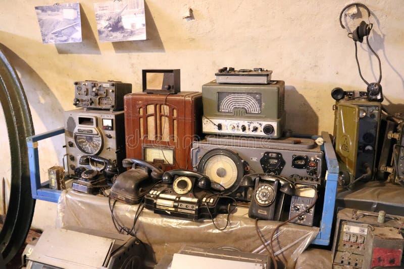 Gamla roterande telefoner, radior och radiostationer på tabellen royaltyfri fotografi