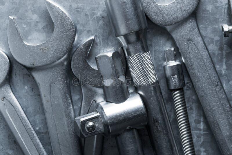 Gamla skiftnyckel och hjälpmedel och motorreservdelar fotografering för bildbyråer